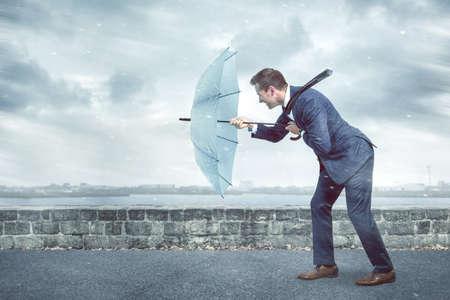 Businessman with an umbrella is facing strong headwind 版權商用圖片