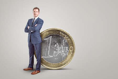 Businessman standing next to an oversized Euro coin