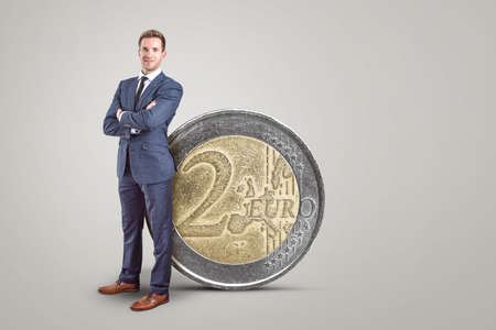 Businessman standing next to an oversized 2 Euro coin 版權商用圖片 - 155359711