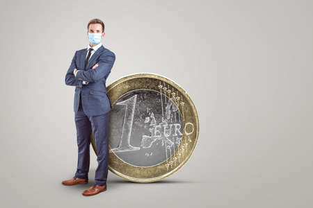 Businessman with a mask standing next to a big Euro coin 版權商用圖片 - 155359712