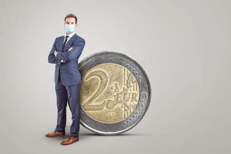 Businessman with a mask standing next to a big 2 Euro coin