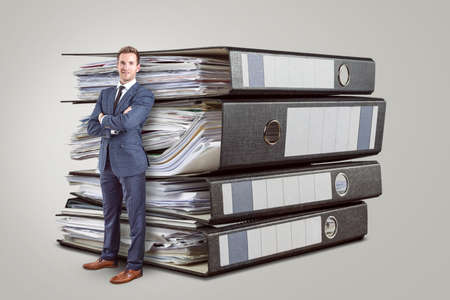 Accountant in front of oversized folders full of paperwork