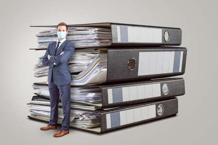 A full length shot of a businessman wearing a protective face mask. He is leaning against an oversized stack of folders. Isolated on a neutral background. Standard-Bild