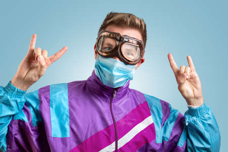 Funny portrait of a young man with goggles and mask going crazy
