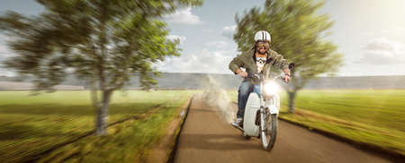 Man with his dog riding a moped at top speed Standard-Bild