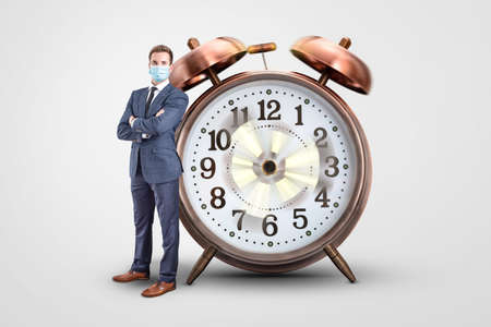Businessman with a mask standing next to a clock with spinning hands