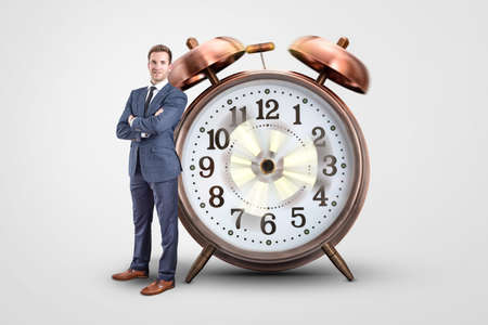 Businessman standing next to an oversized clock with spinning hands