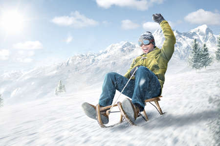 Happy man riding on a sled in winter Standard-Bild