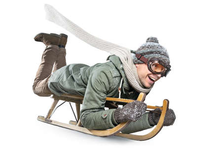 Smiling man riding a sled - isolated on white