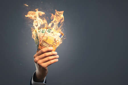 Hand holding burning euro banknotes 版權商用圖片