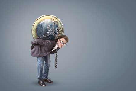Businessman burdened by a large Euro coin