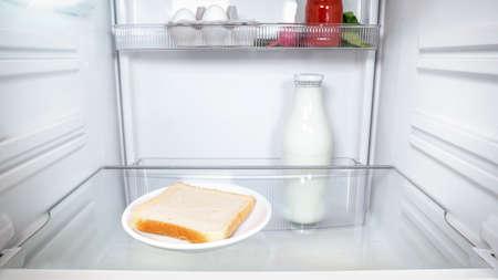 One lonely slice of bread inside an empty fridge