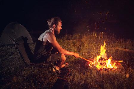 Man camping outdoors at night sitting next to a bonfire