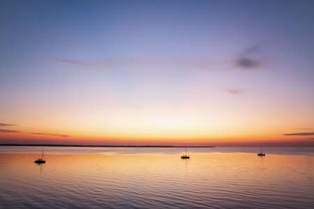Boats anchored in a peaceful bay after sunset at the Baltic Sea