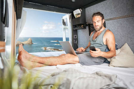 Man inside a camper van using laptop and smartphone