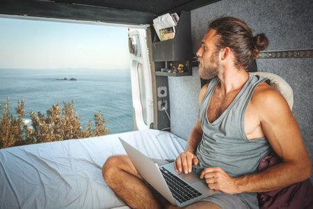 Man with a laptop inside his camper van is looking at the sea 版權商用圖片