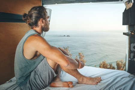 Man sitting in the back of a camper van looking at the sea 版權商用圖片
