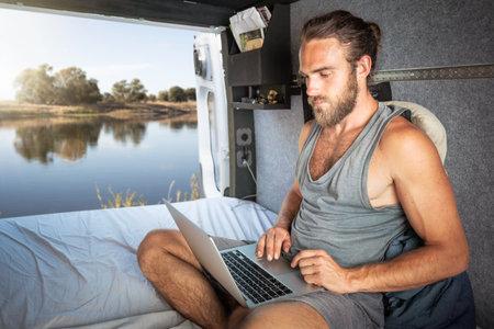 Man using a laptop inside his camper van