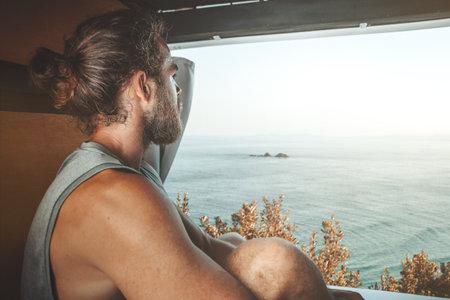 Man in the back of his camper van looking out towards the sea 版權商用圖片