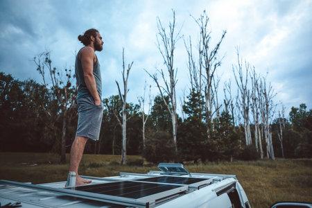 Man on top of his camper van in a moody scenery