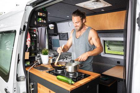 Man cooking on a stove inside his camper van 版權商用圖片