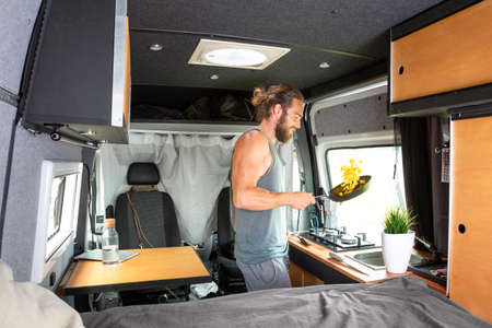 Man inside a camper van is cooking on a gas stove