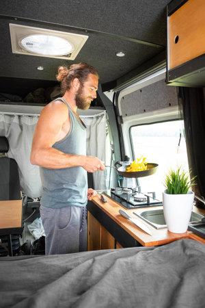 Man cooking food inside his camper van