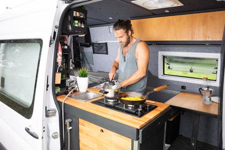 Man cooking in the kitchen area of his camper van 版權商用圖片