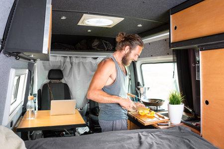 Young man preparing food inside his camper van 版權商用圖片