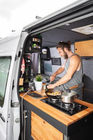 Man cooking inside his camper van 版權商用圖片