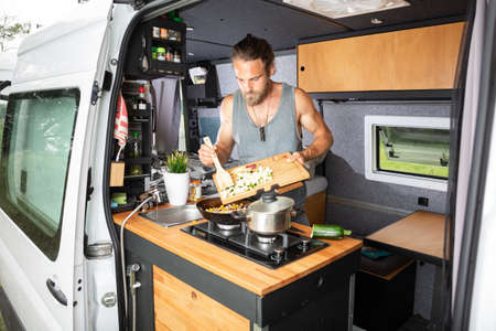 Young man cooking inside his camper van Reklamní fotografie