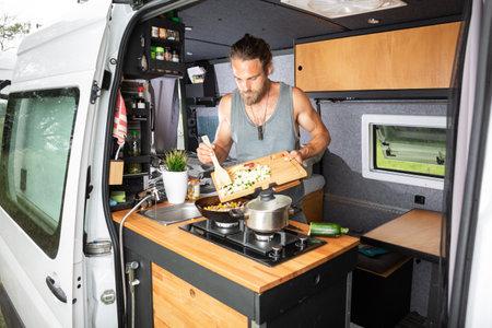 Young man cooking inside his camper van 版權商用圖片