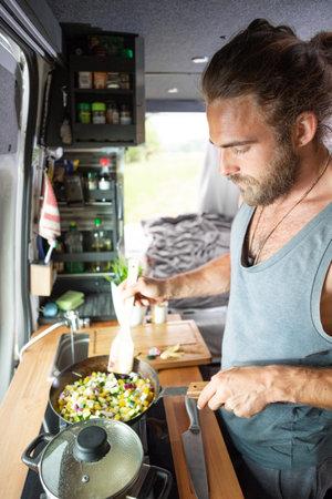 Bearded man preparing vegetables inside his camper van 版權商用圖片