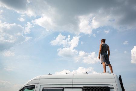Man standing on top of his camper van