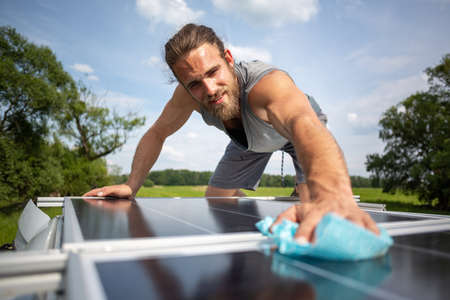 Man wiping a solar panel on the roof of a caravan