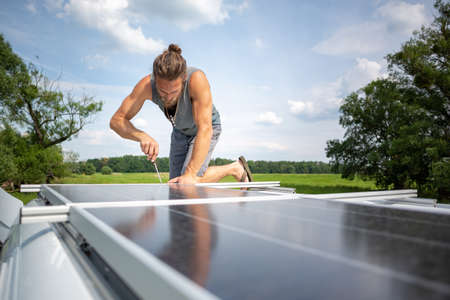Man working on a solar panel on top of a caravan