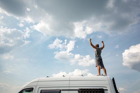 Man with raised arms standing on top of his camper van 版權商用圖片