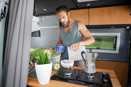 Man preparing breakfast inside a camper van