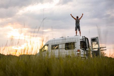 Man with raised arms on top of his camper van