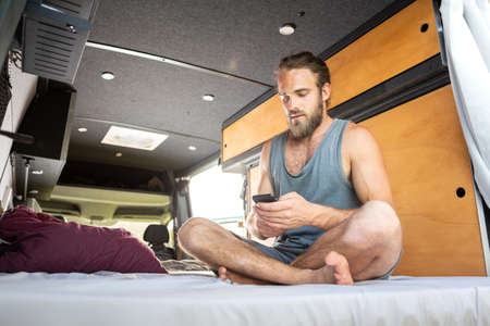 Man sitting on the bed inside a camper van using a smartphone Фото со стока