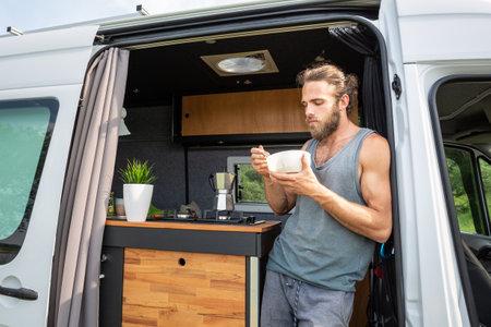 Man having breakfast in the door of his camper van