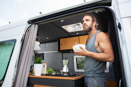 Man having breakfast while standing in his camper van