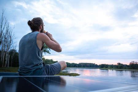 Man having a drink on top of his camper van 版權商用圖片