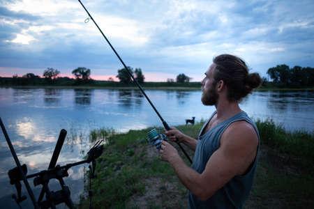 Angler on a river bank at twilight