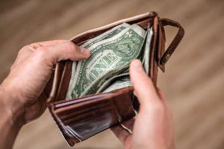 Dollar banknotes inside an open wallet