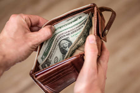 US dollar banknotes inside an open wallet
