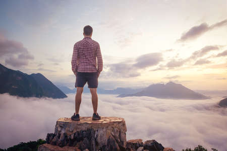 Man standing on a mountain top above the clouds