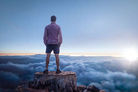 Man on a mountain top enjoying the view over the clouds