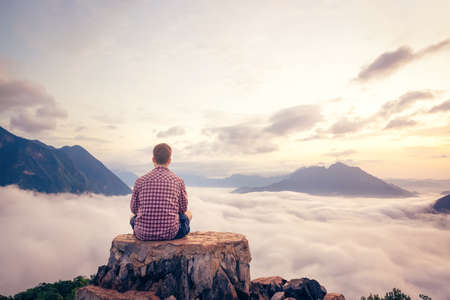 Man sitting on a summit with a beautiful view over the clouds