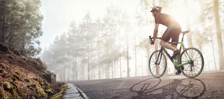 Cyclist with a racing bike riding on a foggy forest road Фото со стока